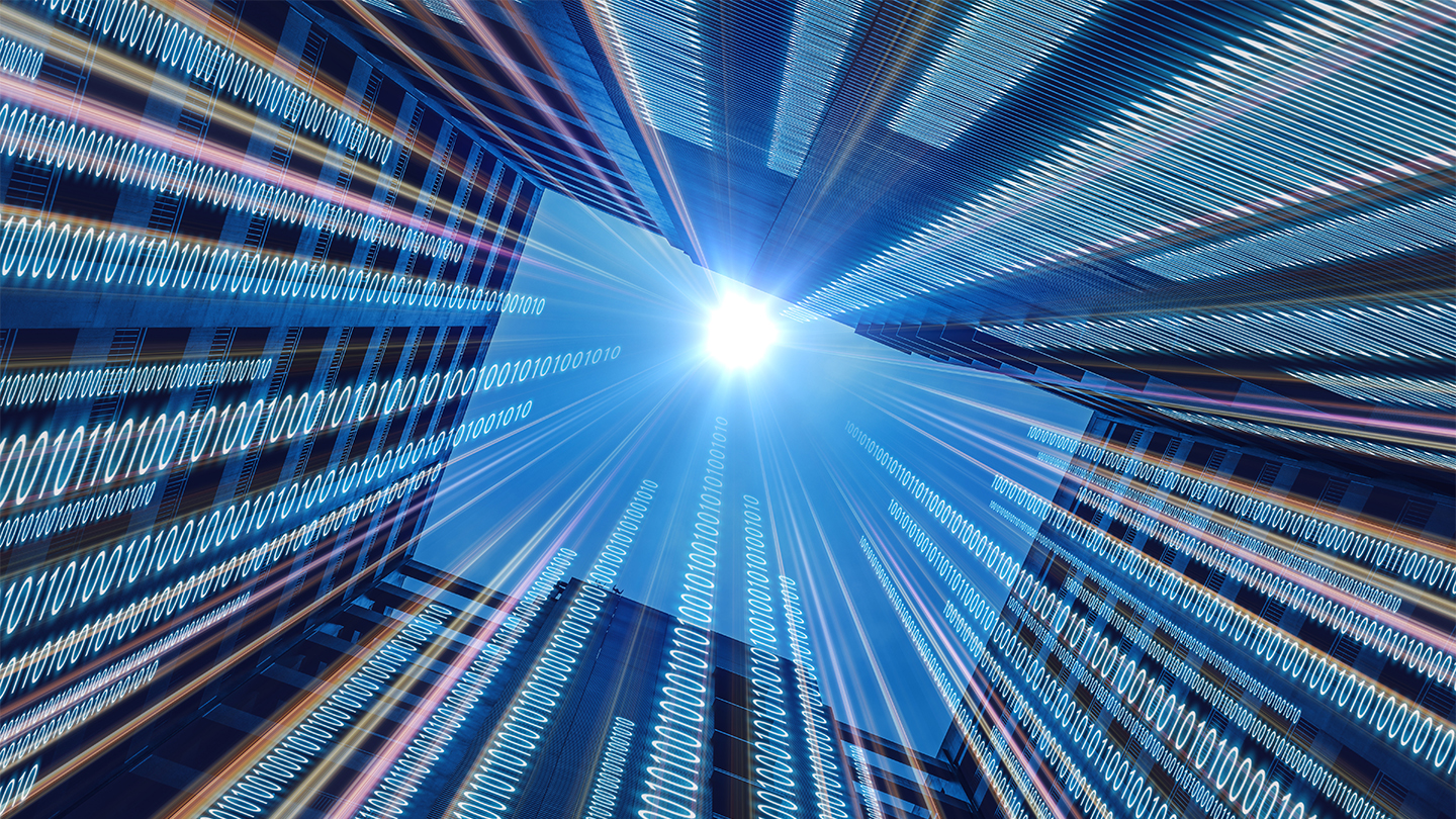 Abstract image of binary code running alongside skyscraper.