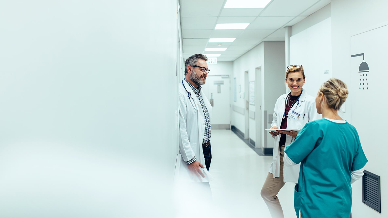 Two doctors speaking to a nurse in hospital hallway.