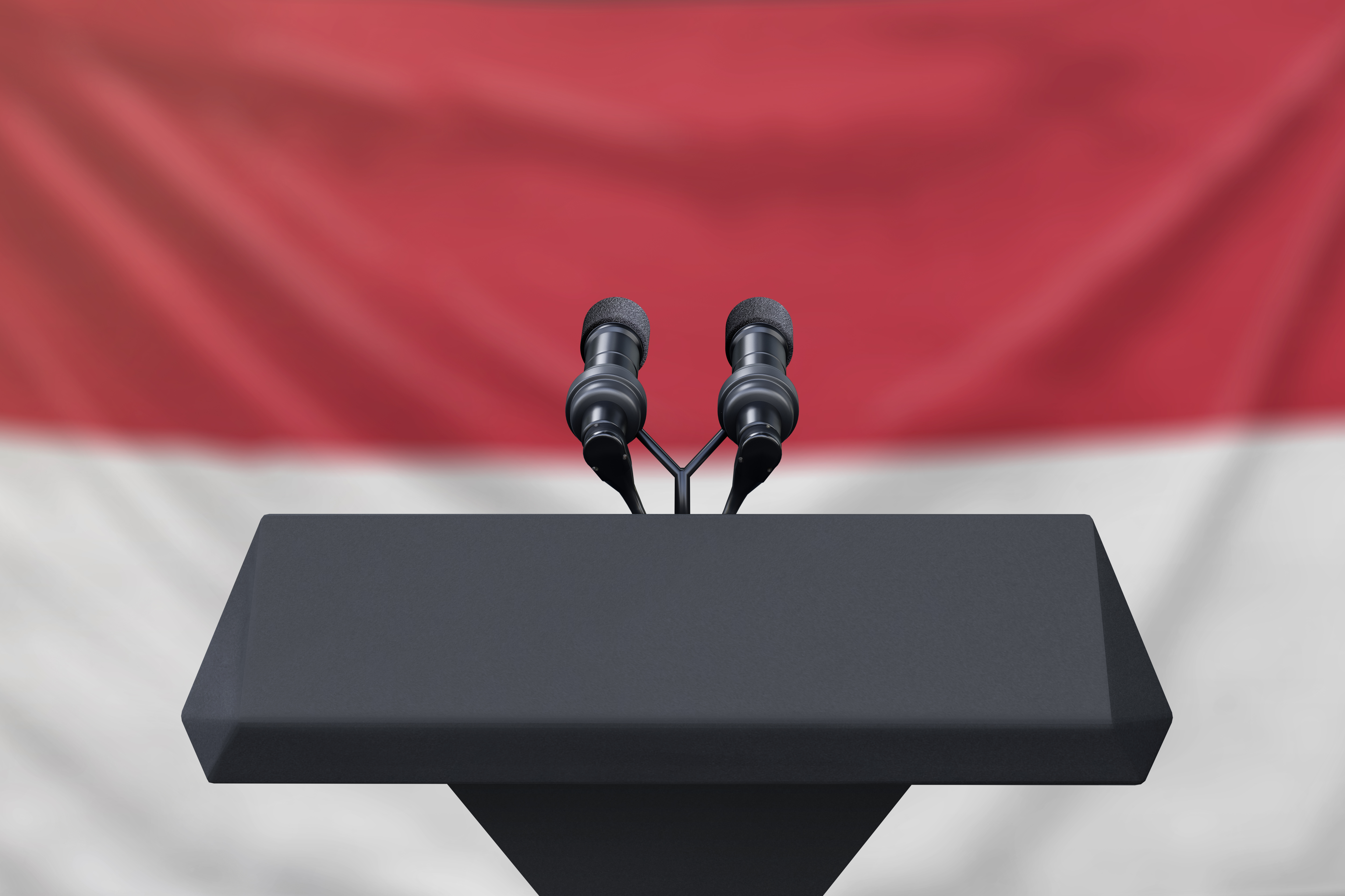 A podium with microphone standing in front of Indonesia's flag