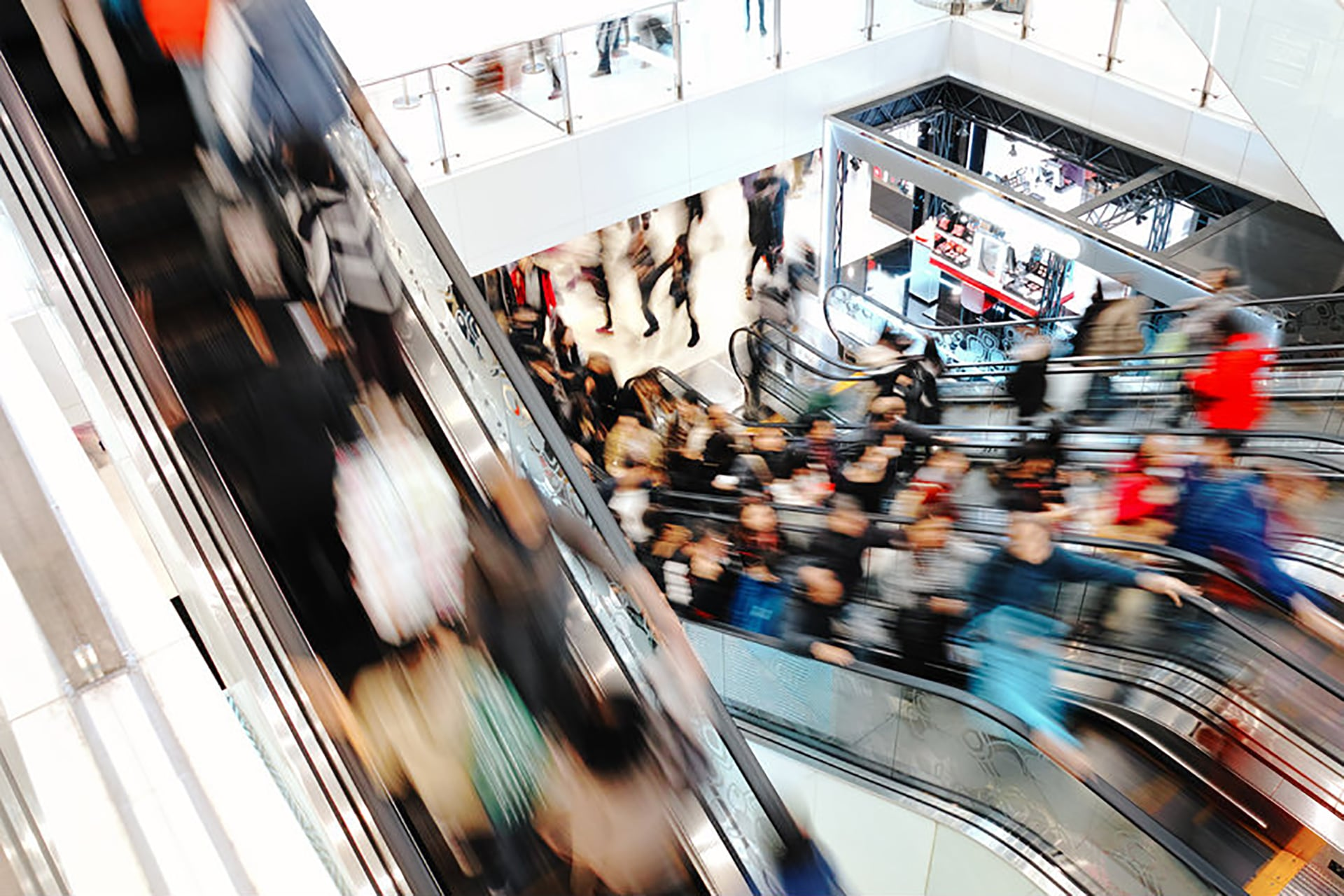 People rushing past on an escalator in a shopping mall.
