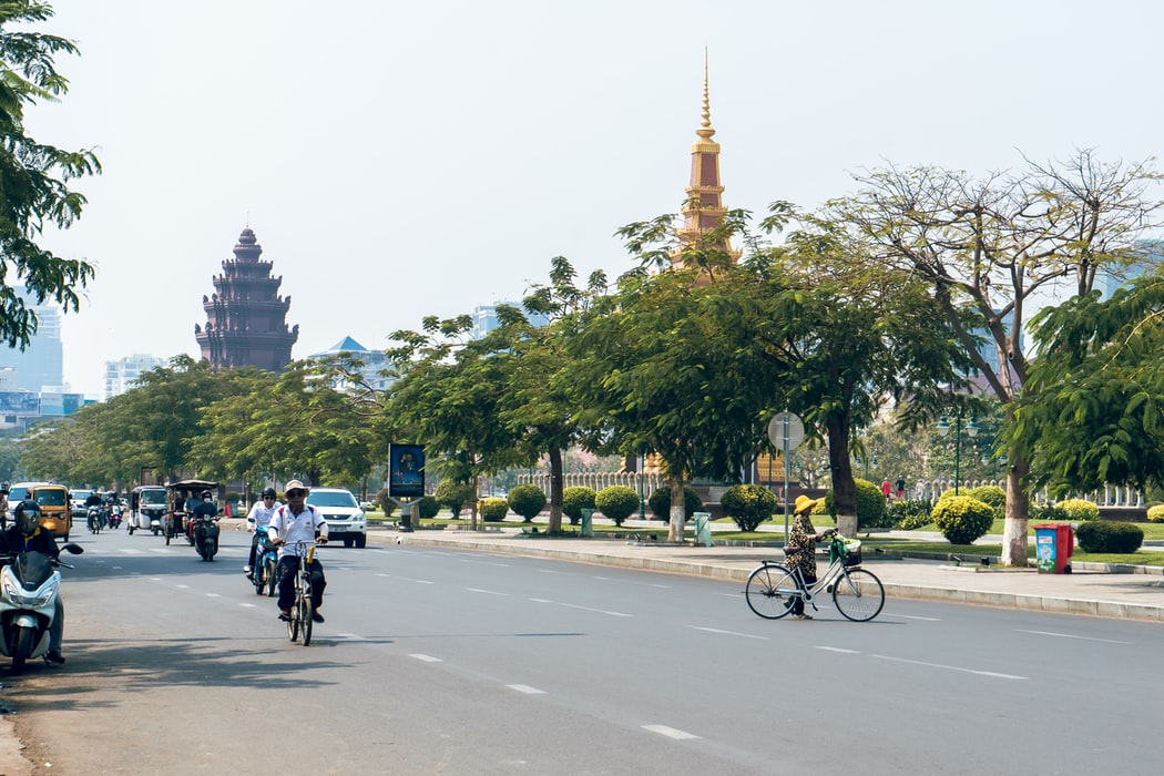 People riding bicycles on a road in Phnom Penh, Cambodia.